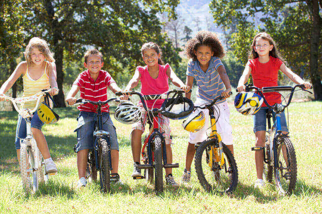Group Of Children Riding Bikes in San Antonio TX not worrying about an accident because they have a great emergency dentist available.