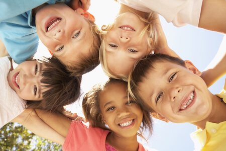 Group of children all with happy bright smiles and the option of sedation dentistry to help with anxiety at Helotes Pediatric Dentistry in San Antonio, TX.