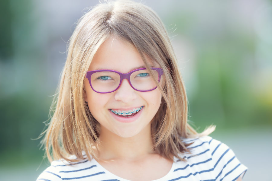 Blonde girl with braces and rubber bands on her braces smiles while wearing purple glasses