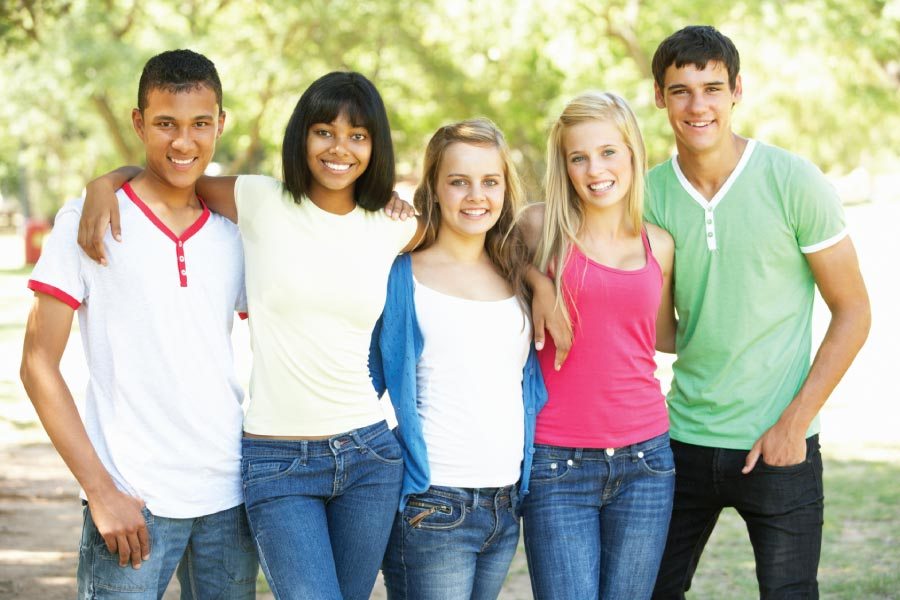 Five smiling teenagers in front of green trees