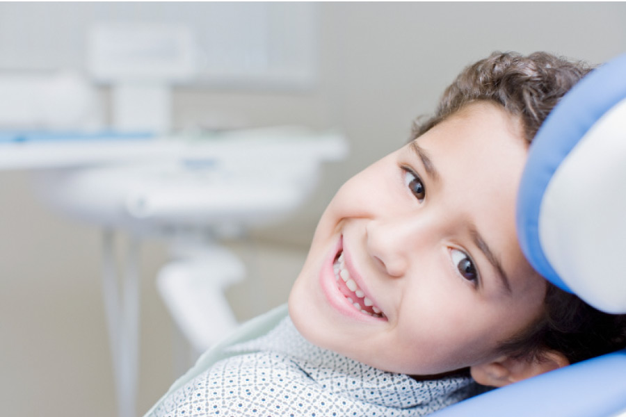 Smiling young dark haired boy in the dental chair