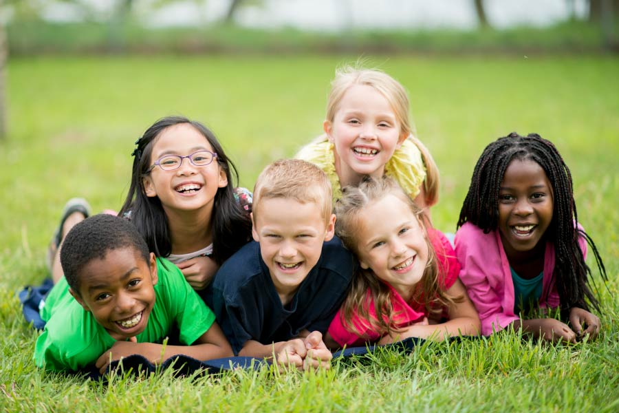 Six smiling multiracial kids piled up on their stomachs on the grass