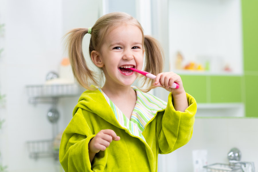 Little blonde girls with pigtails wearing a lime green bathrobe brushes her teeth to avoid cavities.