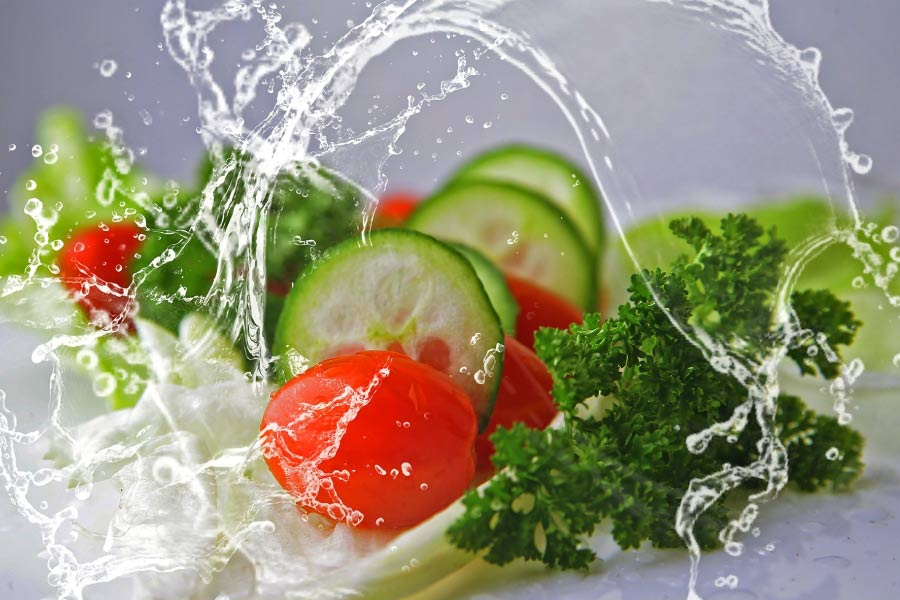 Arc of water splashing over leafy green vegetables, sliced cucumbers & tomatoes.